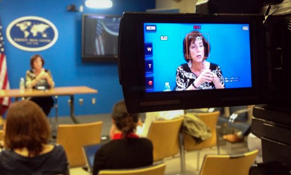 Camera flip screen in the foreground captures a woman speaking on a stage in the background