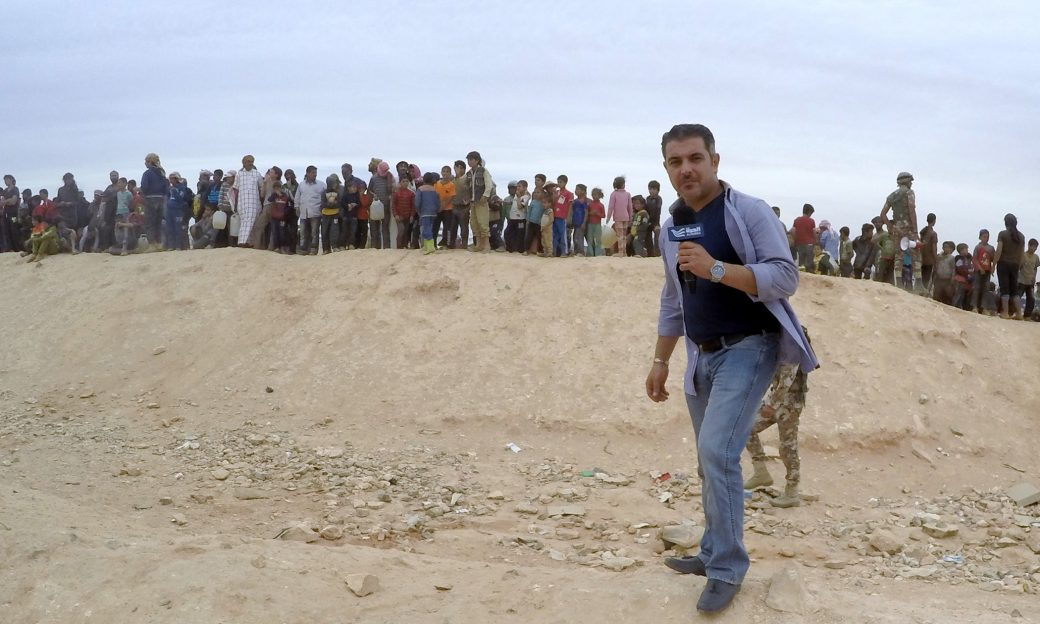 Man speaking into an Alhurra branded microphe, stand on a durt mound with a line of people behind him