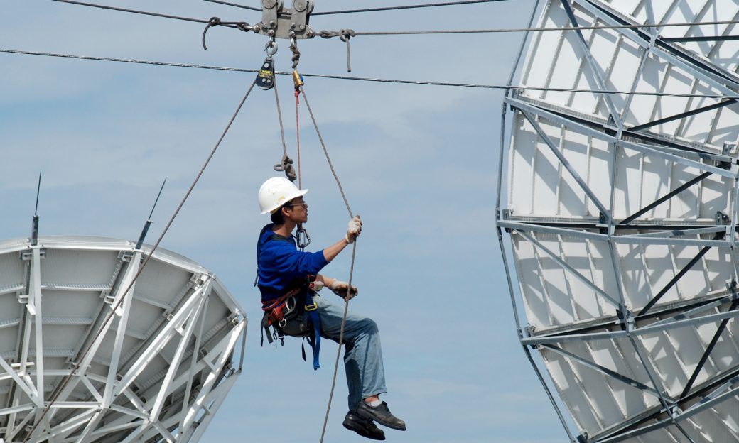Man hangs on a harness from a wire in front of large satellites