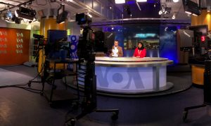 Two VOA television broadcasters sit at a news desk in a studio in front of several cameras