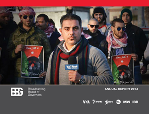Cover of 2014 annual report, shows a reporter in Jordan speaking into a microphone with a crowd behind him.