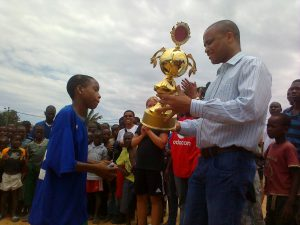A VOA sponsored soccer youth tournament in Mozambique. Here a VOA representative presents a trophy to the winning team.