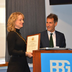 A woman smiles as she receives an award from a man standing at a lectern
