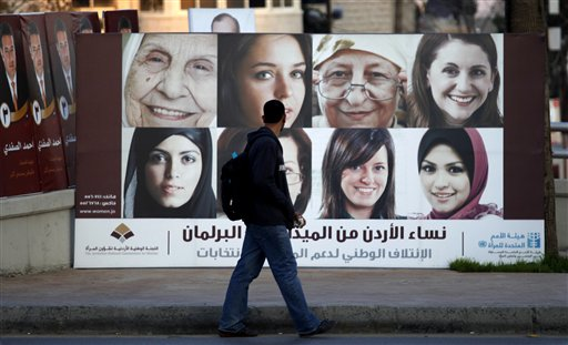 A Jordanian pedestrian passes by a Jordanian parliamentary campaign poster, in Amman