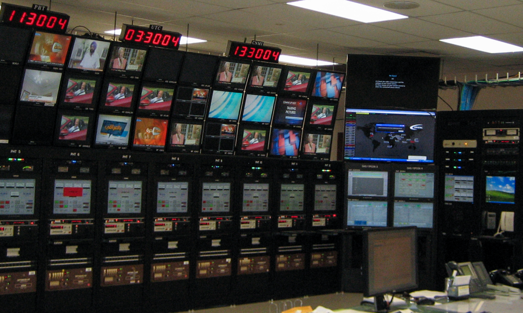 Broadcasting control room with multiple clocks and programming screens
