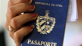 A woman holds up a Cuban passport in a regional immigration office in Havana (Cuba).