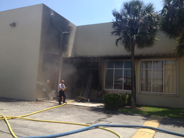 A fire fighter looks at the smoke and fire damage to OCB headquarters in Miami.