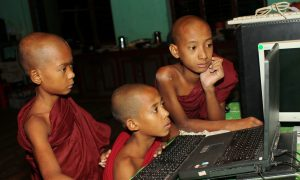 Digital technology is increasingly popular in Burma. Here young monks in training use a computer at a Buddhist monastery.