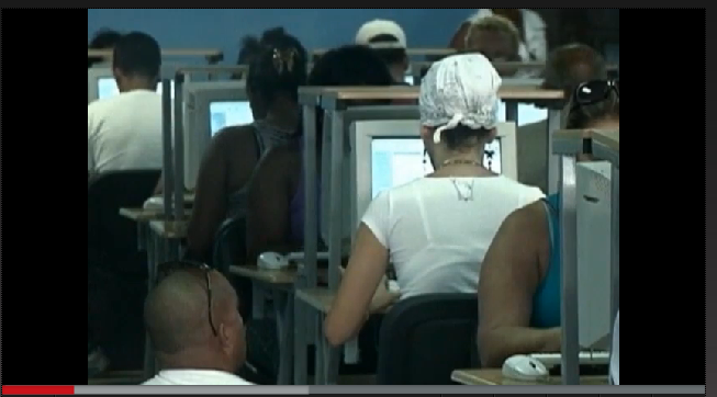 Screengrab from Avanza Cuba episode on Cyber Cafes, shows a row of computers in a cyber cafe with people sitting at each one