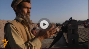 Screengrab from Afghan Brickworks, man in Afghan dress wiping his hands