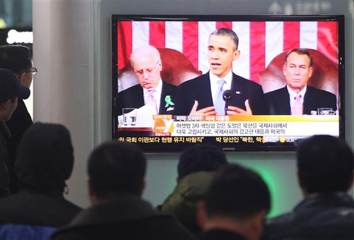 people watching a television that shows Presdient Obama giving hsi 2013 State of the Union speech