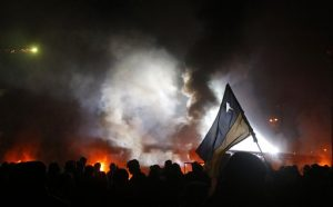Ukrainian flag rises above protestors and fire
