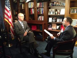 reporter speaks with Congressman, bookshelf and flag in the background