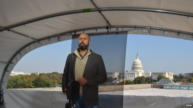 Reporter standing under with tent like cover with U.S. Capitol in the background