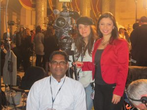 three people, a reporter, producer and a camerman in the rotunda, smile for the camera