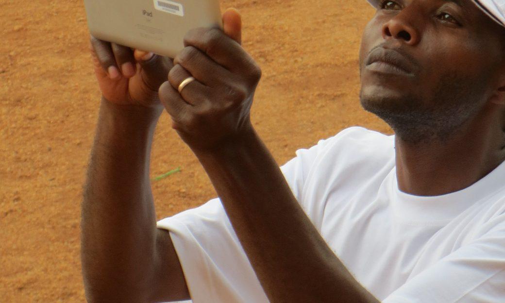 man wearing VOA cap holds up an ipad