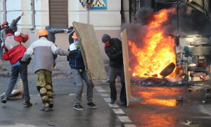 Protestors protect themselves with sheilds during clashes with police