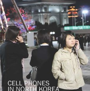 three people on a street using cell phones