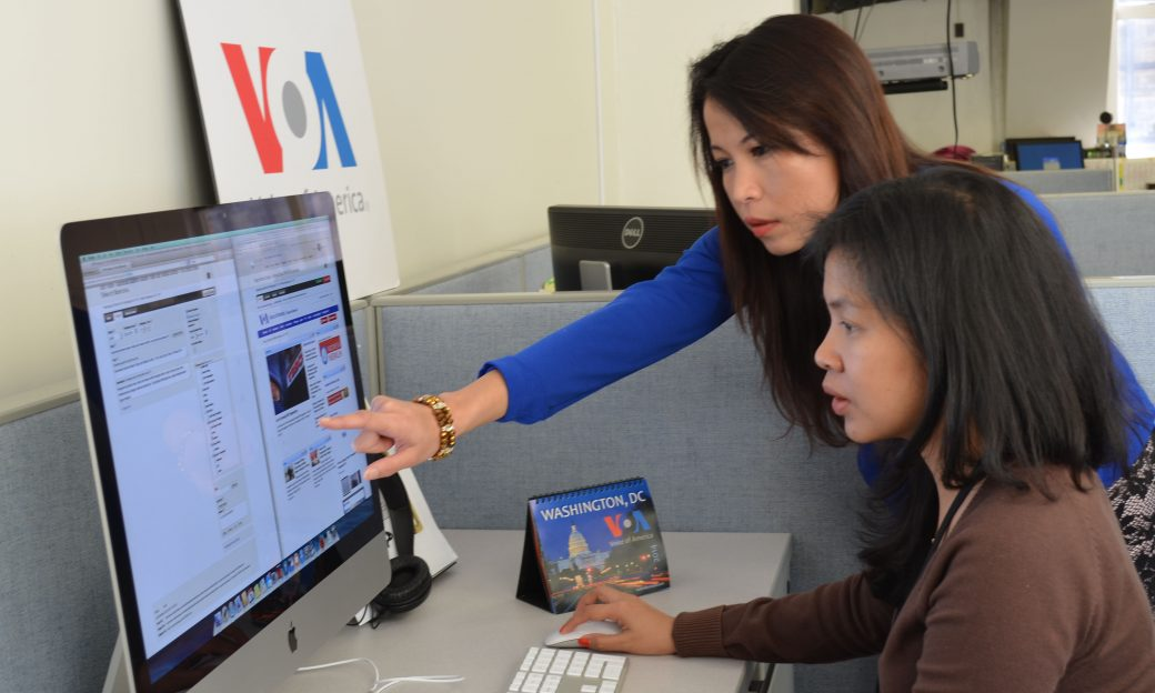 two women at a computer, one pointing to the screen
