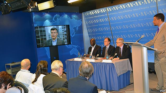 Three men sit on a panel, on man at a podium and another joins via teleconference