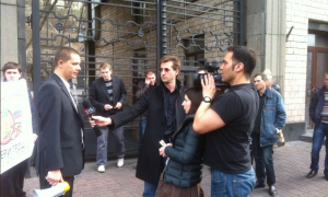 VOA reporter Daniel Schearf and video journalist Arash Arabasadi (with fixer Anna Pyatetska) interview Ukrainian man. Kyiv, Ukraine, March 25, 2014.
