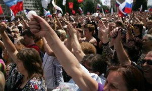 Demonstrators, holding Russian flags, rally for Russian protection