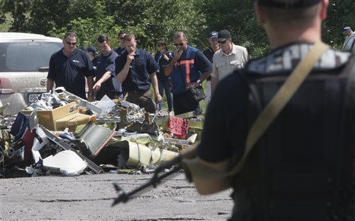 Dutch and Australian investigators along with members of the OSCE mission in Ukraine examine  pieces of the crashed Malaysia Airlines Flight 17