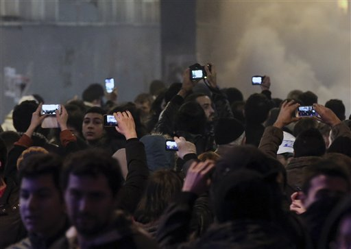 People use mobile devices to record as riot police use a water cannon to disperse protesters during a rally against a bill which would, among other things, allow Turkey's authorities to block web pages for privacy violations without a prior court decision, in Istanbul, Turkey, late Saturday, Feb. 22, 2014. Police in Istanbul have clashed with hundreds of protesters denouncing a new law that increases government controls over the Internet. (AP Photo/Emrah Gurel)