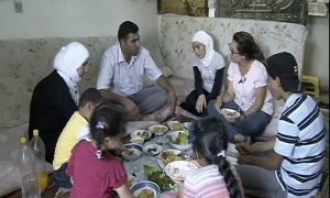 Family sits around table with Iftar meal, celebrating Ramadan.