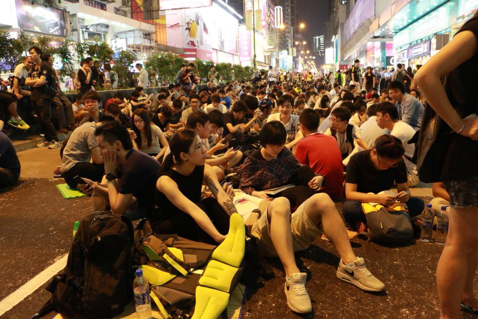 Students in Hong Kong protests sit in street blocking traffic.