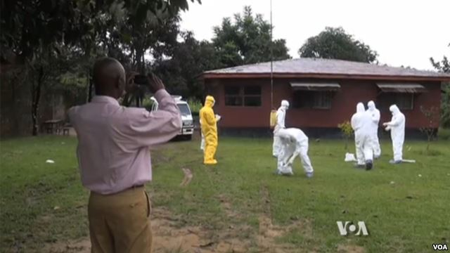 Man takes photo of health workers cleaning up in a grassy area by a home.