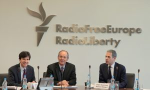 three men sit at a conference table, a sign for Radio Free Europe/Radio Liberty is on the wall behind them