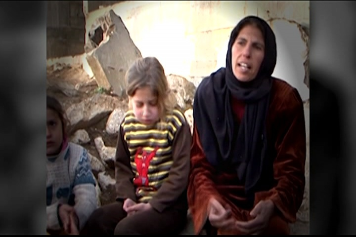 syrian refugees, woman and her child sit on the ground
