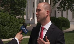 Man outside of the White House speaks into an Alhurra reporter's micrphone