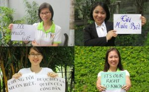 """Vietnamese bloggers display signs demanding government transparency in a """"We Want to Know"""" campaign."""
