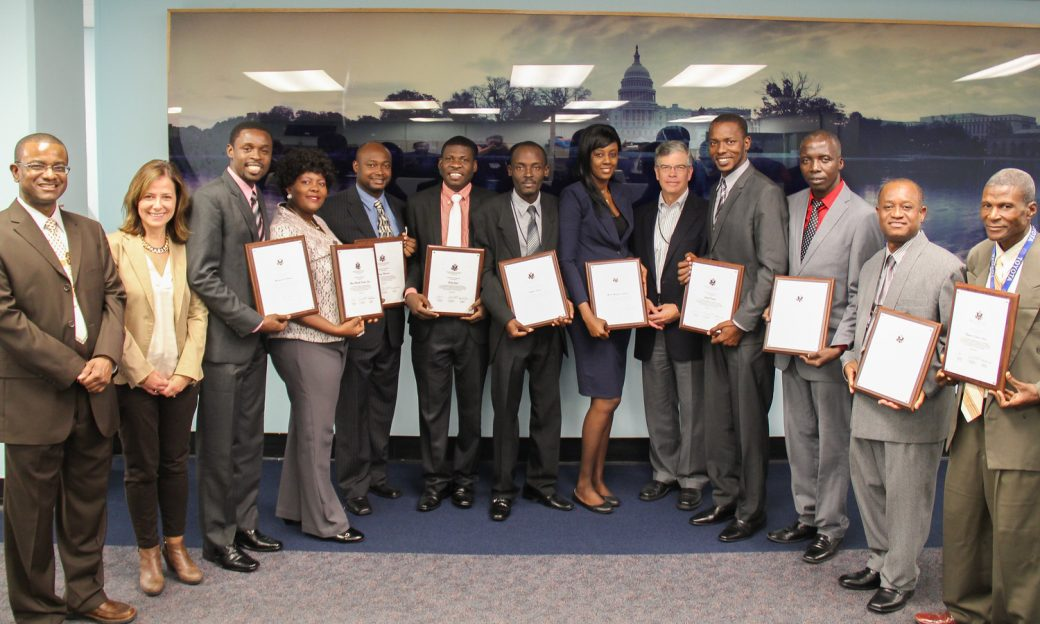 Haitian journalists stand in a line holding plaques, with Creole Service Chief Ronald Cesar, Latin America Division Director Yolanda Lopez, and Deputy IBB Director Jeffrey Trimble