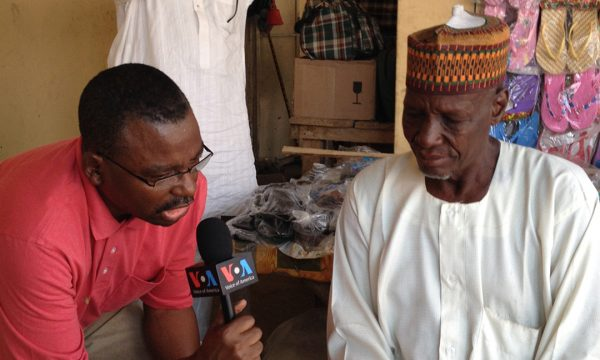 Photo of VOA's Ibrahim Ahmed interviewing man in Nigeria.