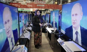A Chechen woman looks at a TV screen with Russian President Vladimir Putin.