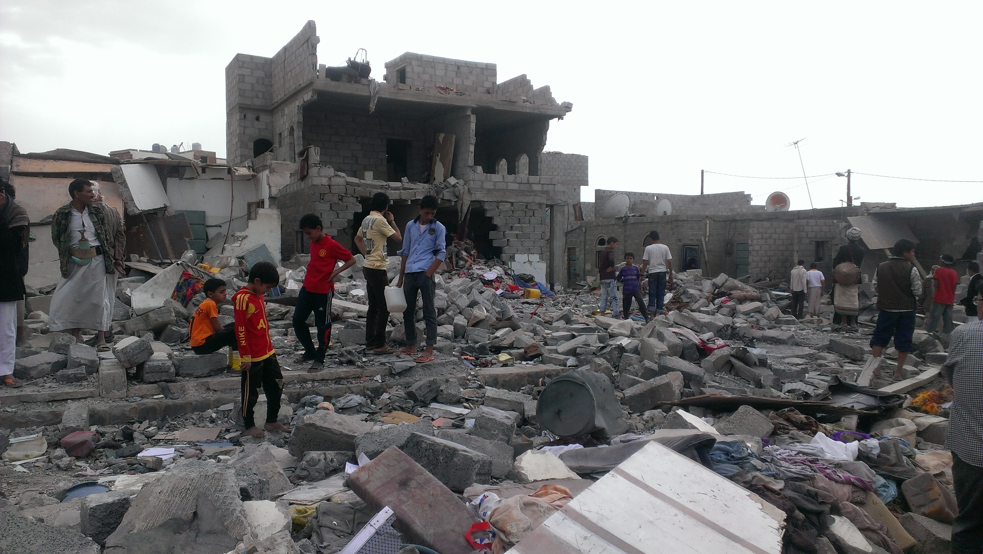 Several people walk among the rubble and debris of destroyed buildings.
