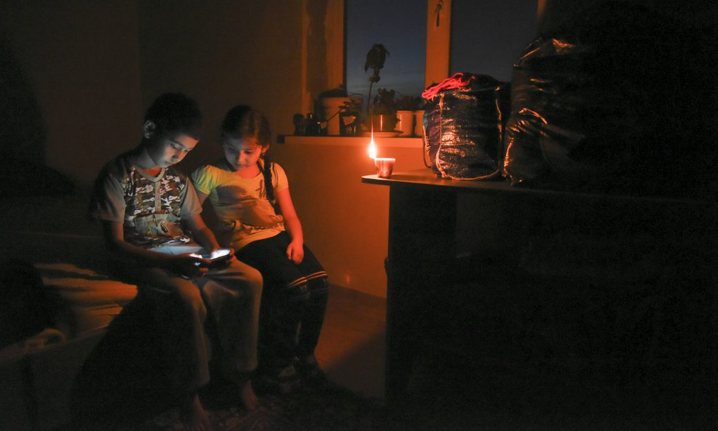 Ethnic Crimean tartar children play on a cell phone in candlelight at their home, after a power failure, in a village outside Simferopol, Crimea.