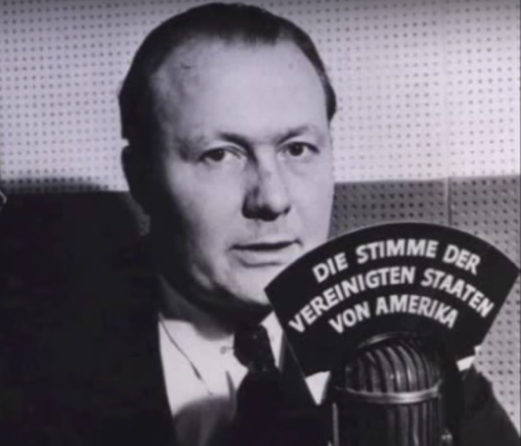 Journalist Robert Bauer at a desk microphone