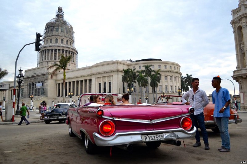 An old red convertible drives by the Cuban capitol building in Havana.