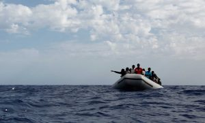 A rubber boat filled with Africans on the open sea.