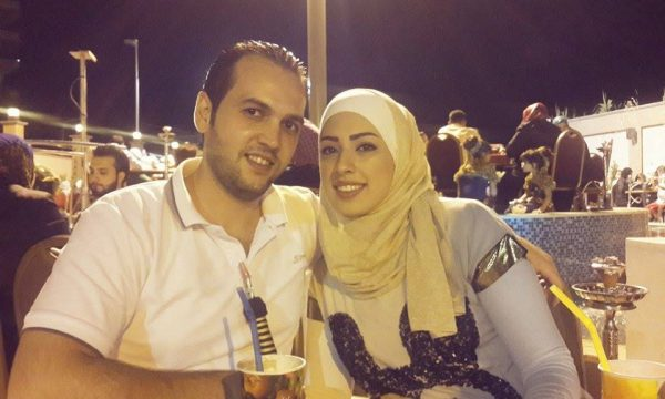 Snapshot of Middle Eastern couple sitting at an outdoor cafe at night.