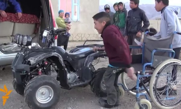 A boy lifts himself off a traditional wheelchair and towards a 4-wheel ATV