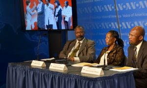 Three people sit on a panel with VOA logos in the background