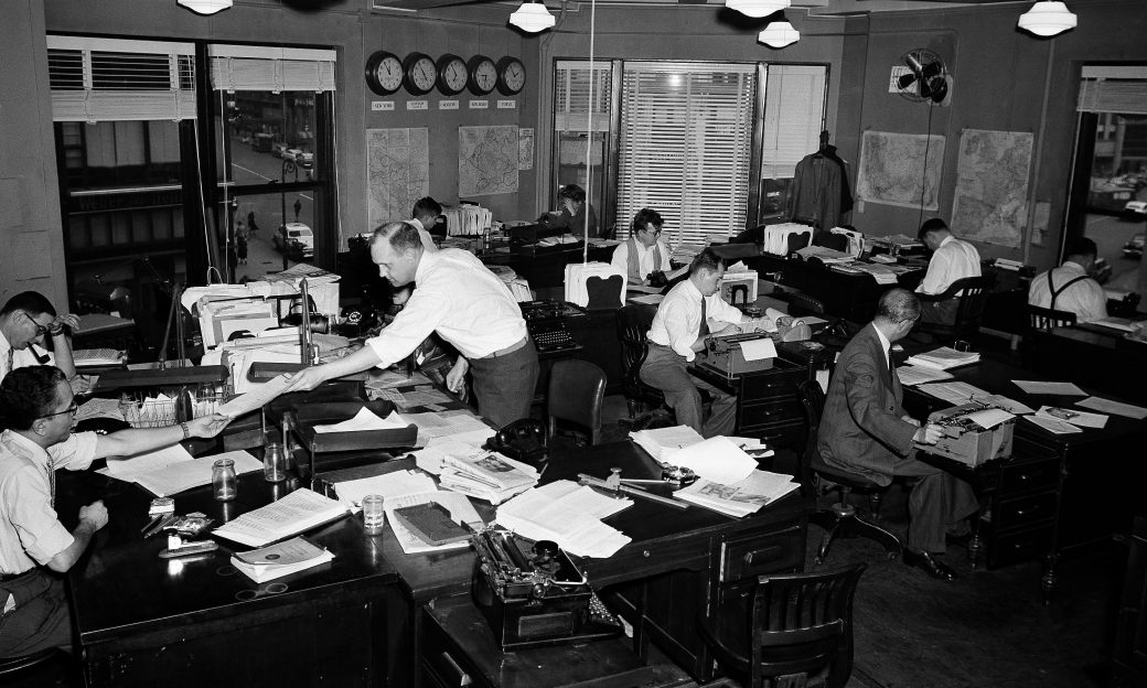 Black-and-white photo of a group of men working at desks in a VOA news room.