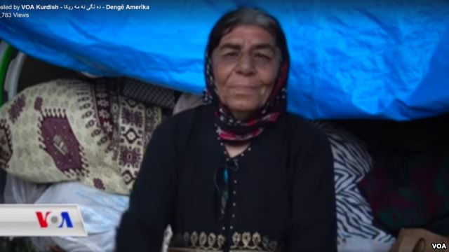 Close up of woman wearing headscarf. She sits in a tent with traditional carpets behind