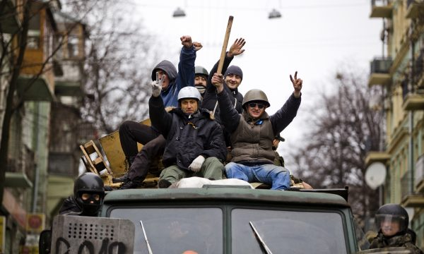 A group of happy men ride on top of a military vehicle
