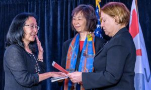 Sandy Sugawara (L) is sworn in by VOA Director Amanda Bennett (R) as the organization's new Deputy Director. Director of Language Programming Kelu Chao, who served as VOA's Acting Director for nearly a year, holds the U.S. Constitution.